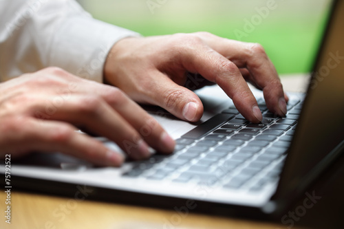 Hands typing on laptop computer poster