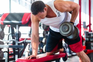 Mann mit Hanteln treibt Sport im Fitnessstudio