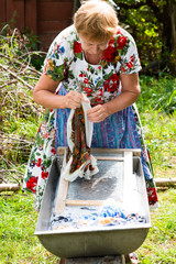 woman washes clothes by hand in a trough in nature, eco