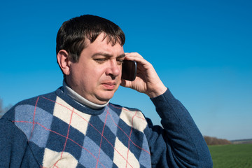 man talking on the phone on nature