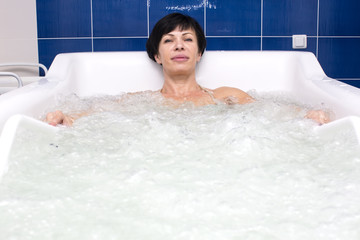 doctor makes a woman a massage at hydrobath