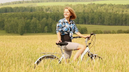 Young woman with bicycle in a wheat field