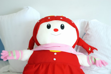 Doll and pillows on bed