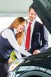 Verkäufer und Kundin mit Neuwagen von Autohaus