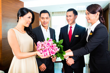 Asian Hotel staff greeting guest with flowers