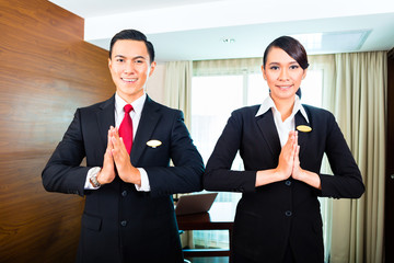 Asian Hotel staff greeting guest in room