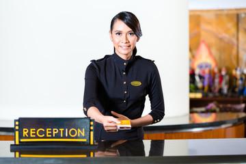 Hotel receptionist passing keycard over conuter