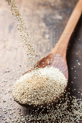 quinoa in a wooden spoon on a background of the dark old wooden