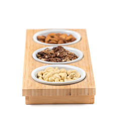Set of assorted nuts in white bowls on wooden stand. Isolated