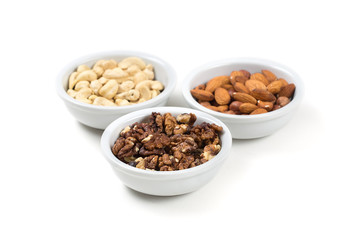 Assorted nuts in white bowls. Isolated on white background