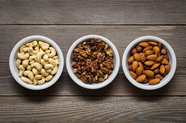 Sorted nuts in white bowls on wooden background