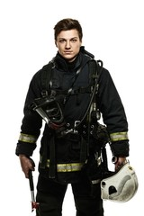 Young firefighter with helmet and axe isolated on white