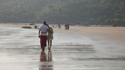 A loving couple walking on the beach