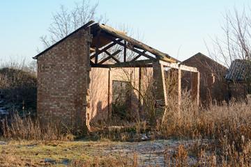 Broken column and roof in derelict barn