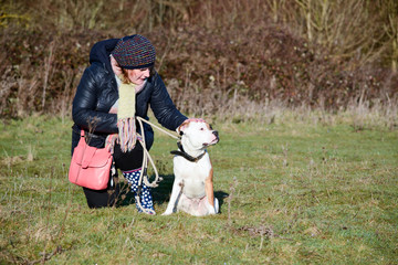 Woman with sitting Staffordshire bull terrier
