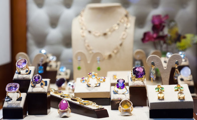 Golden jewelry with gems at showcase