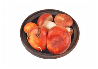 Boletus edulis mushroom in vintage clay bowl, isolated on white