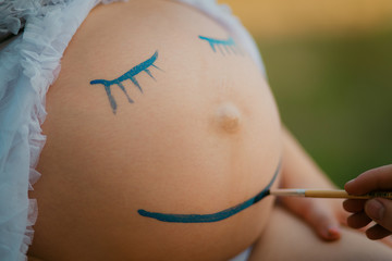 Pregnant woman belly closeup with smiling funny face drawing