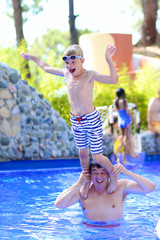 Father and child having fun in water park