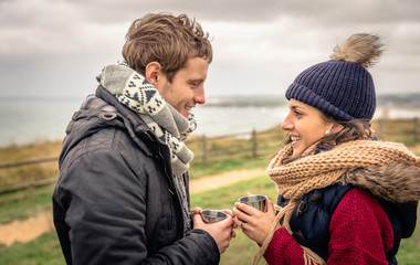 Young couple holding cups of hot drink outdoors in a cold day