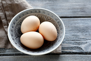 Fresh eggs in a bowl on wooden boards