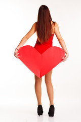 Beautiful girl in red bodi holding paper heart