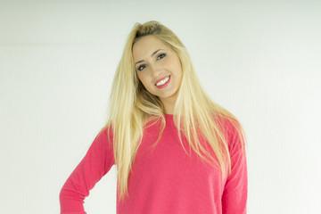 mujer joven rubia europea con sudadera rosa sonriendo