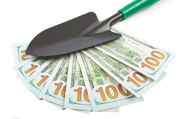 Hundred-dollar bills and garden shovel on white background.