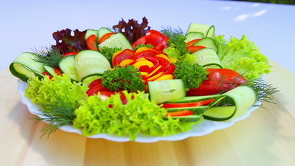 Cutting a variety of fresh, juicy vegetables on a white plate.