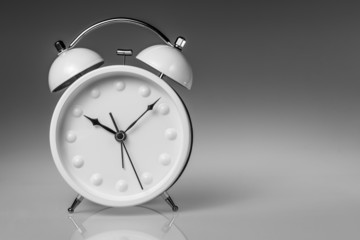 White metal alarm clock with two bells on grey gradient backgrou