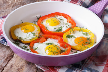 fried eggs with yellow and red peppers in a pan horizontal
