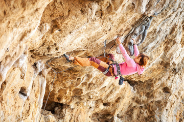 Young female rock climber on face of cliff