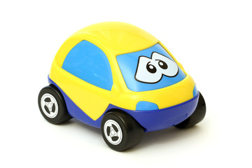 Yellow and blue toy car with eyes isolated on white