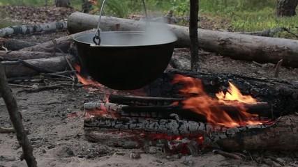 bowler over a campfire