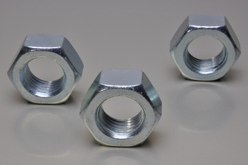Group of steel nuts with light reflection