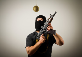 Man in mask with gun and Christmas toy