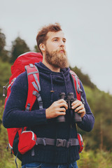 man with backpack and binocular outdoors