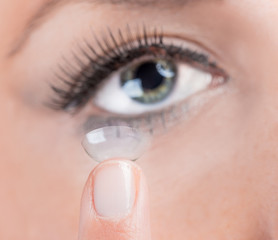Young woman Inserting a contact lens
