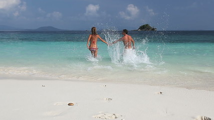 Young couple running into tropical sea