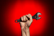 man holding adjustable wrench over red