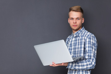 Portrait of confident young man with laptop standing over gray