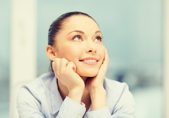 smiling businesswoman dreaming in office