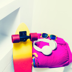 Extreme sports accessories. Skateboard and bright fashionable cl