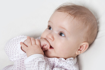 Cute baby girl chewing on her hand