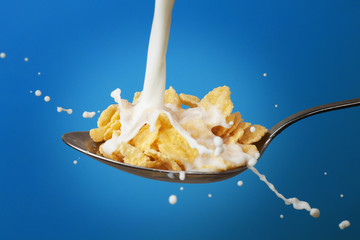 milk splashing into spoon full of cornflakes