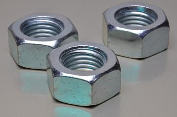 Steel nuts on metal surface
