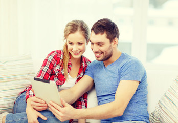 smiling couple with tablet pc computer at home