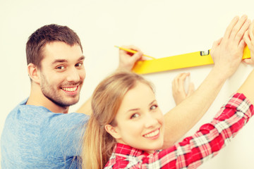 couple building using spirit level to measure