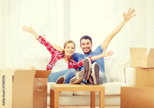 smiling couple relaxing on sofa in new home - 75815516