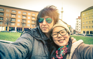 Hipster multiracial couple of tourists taking a selfie in Berlin